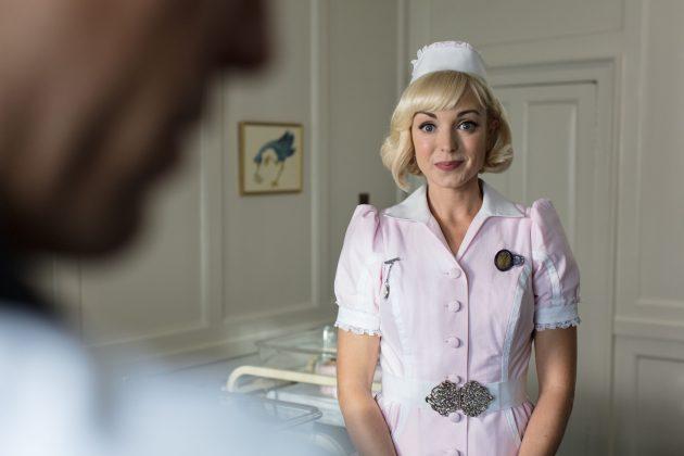 Trixie con un traje de enfermera rosa Llama a la partera