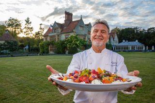 Raymond Blanc presents a delicious dish out vegetables outside Le Manoir Aux Quat' Saisons