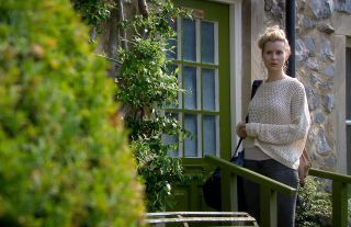 Dawn leaves Woodbine Cottage with a rucksack in Ememrdale