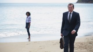 Richard Poole on a beach in Death in Paradise with Camille in the background