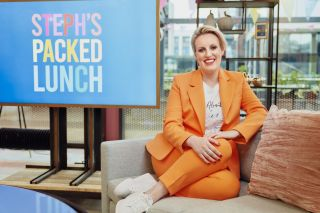 Steph McGovern in a jazzy orange suit on the set of Steph's Packed Lunch